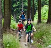 Photo boy, girl and woman riding a bike through the woods along a trail.