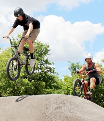 Bike riders using the Youth Activity Park asphalt pump track