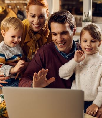 Family waving to computer screen to celebrate holiday