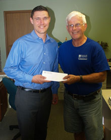 Tim Lohmar hands OASIS Food Pantry a check